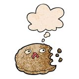 A creative cartoon bitten cookie and thought bubble in grunge texture pattern style. An original creative cartoon bitten cookie and thought bubble in grunge stock illustration
