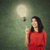 Creative casual woman pointing at lamp Royalty Free Stock Photos