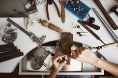 Creative chaos. Top view of jeweler`s workbench with different tools for making jewelry. Female jeweler`s hands. Polishing a silver ring with grinding machine stock image