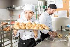 Creative Chef Taking Aroma Of Baked Pastries. Female station chef smelling yummy pastries in restaurant royalty free stock photography