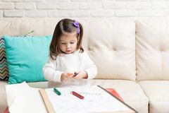 Creative Child Drawing At Home. Cute little girl drawing with colorful crayons while sitting on sofa at home stock photography