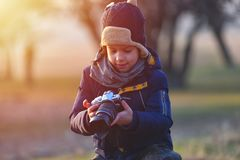 Creative child, kid photographer a little boy with a camera taking landscape pictures in warm sunset light stock photo
