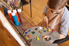 Creative child using pallet in the art studio. Creating my piece of art. Attentive involved skillful child sitting in the art studio and having pictorial class Royalty Free Stock Photos