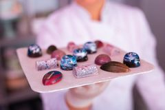 Experienced confectioner looking at plate with creative chocolates. Creative chocolates. Experienced professional confectioner looking at plate with beautiful stock photo