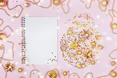 Creative christmas background of holiday ball with decoration and clean notebook for planning on pink table top view. Flat lay royalty free stock photo
