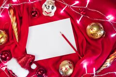 A clean white sheet of paper and a red pencil lie on the blanket, and next to them are red and gold Christmas balls, Santa`s hat