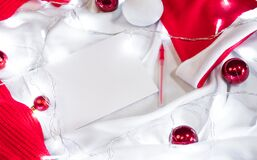 Creative Christmas banner and wish list sheet. A clean white sheet of paper and a red pen lie on a blanket, and next to them are