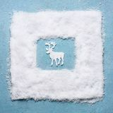 Creative Christmas concept with white deer in snow frame on light blue background, top view. royalty free stock photo