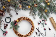 Creative christmas diy. Woman making handmade xmas wreath. Home leisure, tools, trinkets and details for holiday. Decorations on white table background. Top royalty free stock photography