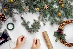 Creative christmas diy. Woman making handmade xmas wreath. Home leisure, tools, trinkets and details for holiday. Decorations on white table background. Top royalty free stock images