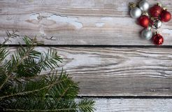 Creative Christmas layout with red and silver ornament. And fir on the wooden background royalty free stock images