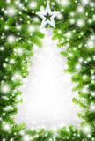 Creative Christmas tree border. Border made of fir twigs and snow building the empty shape of a Christmas tree Stock Photos
