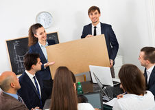 Creative colleagues discussing new development plan at poster Royalty Free Stock Photo