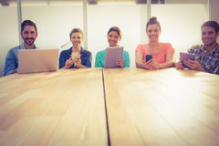 Creative colleagues with laptop and digital tablet smiling at camera. In the office stock photo