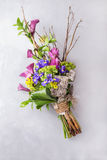 Creative colorful bouquet of iris and orchid and wooden branches. Still life with colorful flowers. Fresh flowers. Place for text. Stock Images