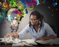 Creative and colorful idea. Man reads books with above colored bulb Royalty Free Stock Images