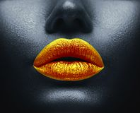 Creative colorful makeup. Bodyart, lipgloss on sexy lips, girls mouth. Golden lips on black skin