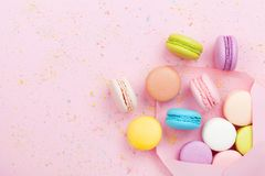 Creative composition with envelope and cake macaron or macaroon on pink pastel background top view. Flat lay. stock image
