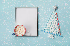 Creative composition with hot cocoa or chocolate, silver frame and fir tree made of marshmallow on winter desk. Christmas mockup. Creative composition with cup Stock Photo