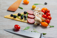 Creative composition of ingredients tomatoes, cheese, salami, mushrooms, arugula, olives in the form of a slice of pizza.  Royalty Free Stock Image