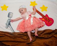 Creative composition. Little baby girl laying near drawn guitar, microphone and stars stock image