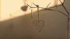 Creative composition in neutral colors for Valentine`s Day. Hearts on a branch in a vase on the table.