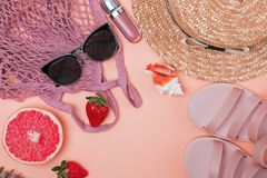 Creative composition with pink sandals, net bag, sunglasses and other. Summer travel accessories concept. Creative composition with pink sandals, net bag stock photo