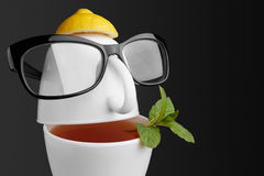 Creative composition on the theme of tea. Tea cups in the form of a human face with glasses Stock Photography