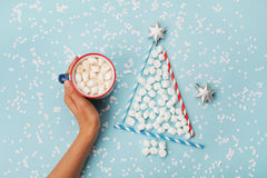 Creative composition with woman hand hold cup of hot cocoa or chocolate and christmas fir tree made of marshmallow on blue desk. Royalty Free Stock Photos
