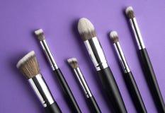 Beauty brushes. Creative concept beauty fashion photo of cosmetic product make up brushes kit on purple background royalty free stock image