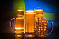 Creative concept. Beer glasses on table at dark toned foggy background with blurred view of flag of Sweden. Support your country w stock image