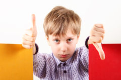 Creative concept of a blond Caucasian boy showing gestures. Cool and bad with two colorful books Stock Photo
