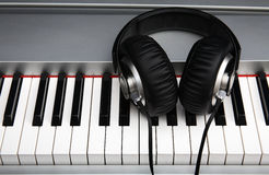 Creative concept of a digital piano keyboard with big black leather headphones. Creative concept of a digital piano keys with big black leather headphones Royalty Free Stock Photos