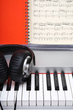 Creative concept of a digital piano keys with big black leather headphones. And piano music Royalty Free Stock Image