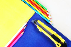 Creative concept of multicolored pencils lying on colorful shee. Creative concept of multicolored pencils and a paper knife lying on colorful sheets of paper Stock Photography