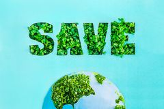 Creative concept with outline lettering Save in green fresh grass sprouts and part of planet model on blue turquoise background. S. Ave Earth, nature. Earth Day Stock Photos