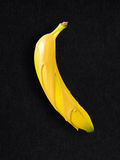 Banana over gold. Creative concept photo of a banana covered with gold paint on black background Royalty Free Stock Photo