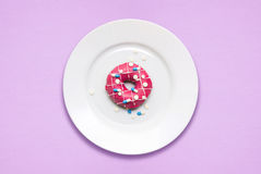 Sweet dreams. Creative concept photo of a donut covered with pills on a plate on pink/blue background Stock Photo