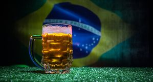 Creative concept. Pint of fresh beer on grass with blurred flag of Brazil on background or Glass of lager beer ready for drink. Co. Py space. Selective focus royalty free stock image