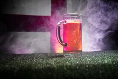 Creative concept. Pint of fresh beer on grass with blurred flag of England on background or Glass of lager beer ready for drink. C. Opy space. Selective focus royalty free stock images