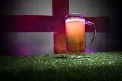 Creative concept. Pint of fresh beer on grass with blurred flag of England on background or Glass of lager beer ready for drink. C. Opy space. Selective focus royalty free stock photo