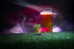 Creative concept. Pint of fresh beer on grass with blurred flag of Germany on background or Glass of lager beer ready for drink. C. Opy space. Selective focus royalty free stock photos
