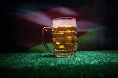 Creative concept. Pint of fresh beer on grass with blurred flag of Germany on background or Glass of lager beer ready for drink. C. Opy space. Selective focus stock image