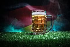 Creative concept. Pint of fresh beer on grass with blurred flag of Germany on background or Glass of lager beer ready for drink. C stock photography