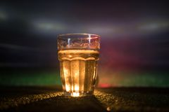 Creative concept. Pint of fresh beer on grass blurred stadium on background with fog and light. Glass of lager beer ready for drin. Creative concept. Pint of royalty free stock images