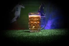Creative concept. Pint of fresh beer on grass blurred stadium on background with fog and light. Glass of lager beer ready for drin. Creative concept. Pint of royalty free stock photo