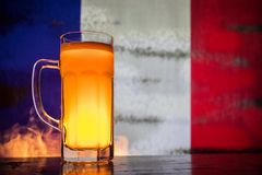 Creative concept. Pint of fresh beer on table with blurred flag of France on background or Glass of lager beer ready for drink. Co. Py space. Selective focus royalty free stock image