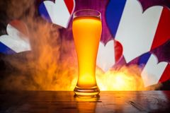 Creative concept. Pint of fresh beer on table with blurred flag of France on background or Glass of lager beer ready for drink. Co. Py space. Selective focus royalty free stock images