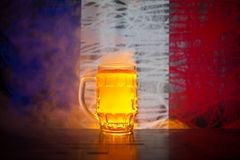 Creative concept. Pint of fresh beer on table with blurred flag of France on background or Glass of lager beer ready for drink. Co. Py space. Selective focus royalty free stock photography