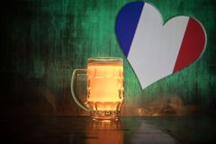 Creative concept. Pint of fresh beer on table with blurred flag of France on background or Glass of lager beer ready for drink. Co. Py space. Selective focus stock image